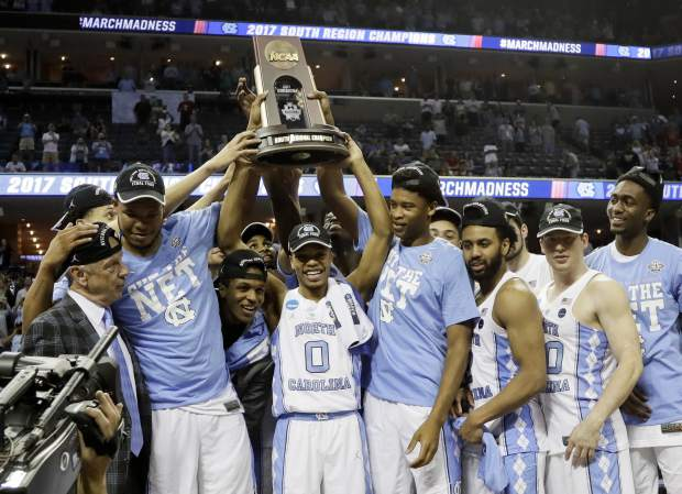 North Carolina players and coaches celebrate after beating Kentucky 75-73 in the South Regional final game in the NCAA college basketball tournament Sunday, March 26, 2017, in Memphis, Tenn. (AP Photo/Mark Humphrey)