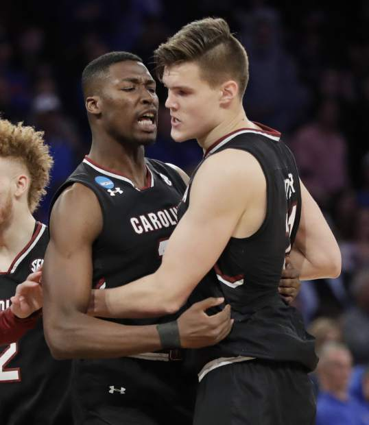 South Carolina forward Sedee Keita, left, congratulates forward Maik Kotsar (21) after Kotsar scored against Florida during the second half of the East Regional championship game of the NCAA men's college basketball tournament, Sunday, March 26, 2017, in New York. (AP Photo/Julio Cortez)