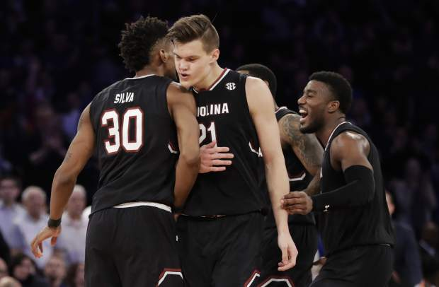 South Carolina forward Maik Kotsar (21) is congratulated by forward Chris Silva (30) after scoring against Florida during the second half of the East Regional championship game of the NCAA men's college basketball tournament, Sunday, March 26, 2017, in New York. (AP Photo/Julio Cortez)