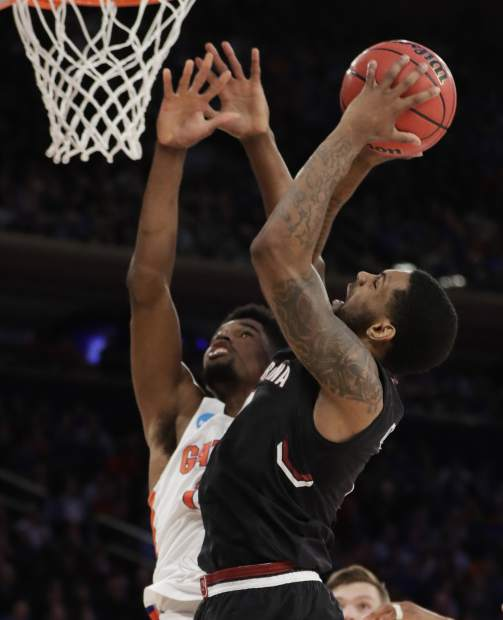 South Carolina guard Sindarius Thornwell (0) puts up a shot against Florida forward Kevarrius Hayes (13) during the second half of the East Regional championship game of the NCAA men's college basketball tournament, Sunday, March 26, 2017, in New York. (AP Photo/Julio Cortez)