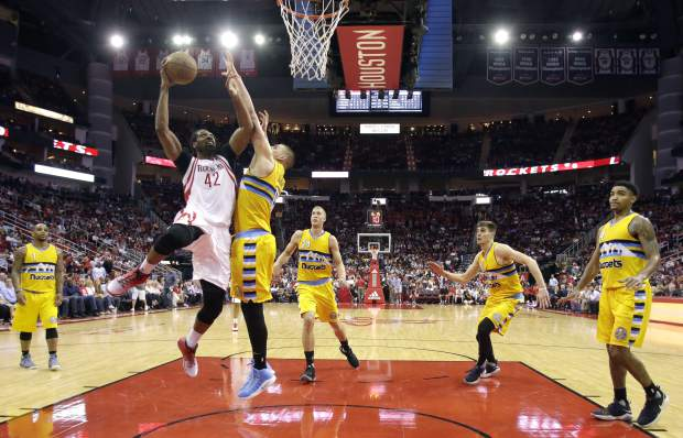 Houston Rockets' Nene (42) shoots as Denver Nuggets' Nikola Jokic defends during the second half of an NBA basketball game Monday, March 20, 2017, in Houston. The Rockets won 125-124. (AP Photo/David J. Phillip)