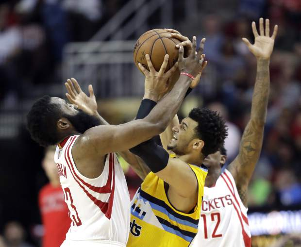 Denver Nuggets' Jamal Murray, center, tries to keep the ball from Houston Rockets' James Harden, left, during the second half of an NBA basketball game Monday, March 20, 2017, in Houston. The Rockets won 125-124. (AP Photo/David J. Phillip)