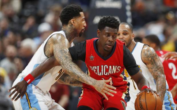 New Orleans Pelicans guard Jrue Holiday, right, dribbles next to Denver Nuggets forward Wilson Chandler during the second half of an NBA basketball game Sunday, March 26, 2017, in Denver. The Pelicans won 115-90. (AP Photo/David Zalubowski))