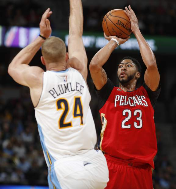 New Orleans Pelicans forward Anthony Davis, right, throws a three-point basket over Denver Nuggets center Mason Plumlee as time runs out in the first quarter of an NBA basketball game Sunday, March 26, 2017, in Denver. (AP Photo/David Zalubowski))
