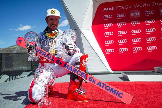 Austria's Marcel Hirscher poses with his crystal globe awards on the podium on Sunday at Aspen Mountain.