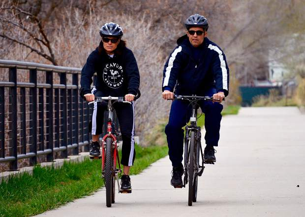 Two bicyclists enjoy Glenwood Springs riverfront trail at midday Monday.