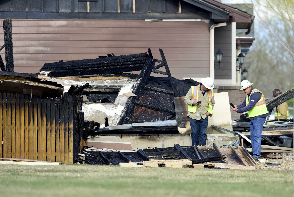 In this April 18, 2017, photo, workers are seen near a house that was destroyed in a deadly explosion in Firestone, Colo., on April 17. Anadarko Petroleum said Wednesday, April 26, that it operated a well about 200 feet (60 meters) from the house in the town of Firestone. The company didn't say whether the well was believed to be a factor in the explosion or whether it produced oil, gas or both.