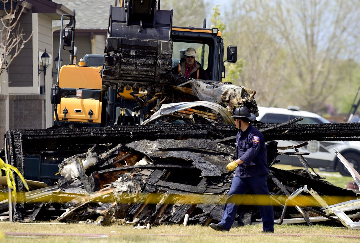 In this April 18, 2017, photo, investigators stand by as debris is removed from a house that was destroyed in a deadly explosion in Firestone, Colo., on April 17. Anadarko Petroleum said Wednesday, April 26, that it operated a well about 200 feet (60 meters) from the house in the town of Firestone. The company didn't say whether the well was believed to be a factor in the explosion or whether it produced oil, gas or both.