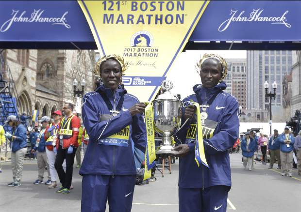 Edna Kiplagat, left, and Geoffrey Kirui, both of Kenya, hold a trophy together after their victories in the 121st Boston Marathon on Monday, April 17, 2017, in Boston. (AP Photo/Elise Amendola)