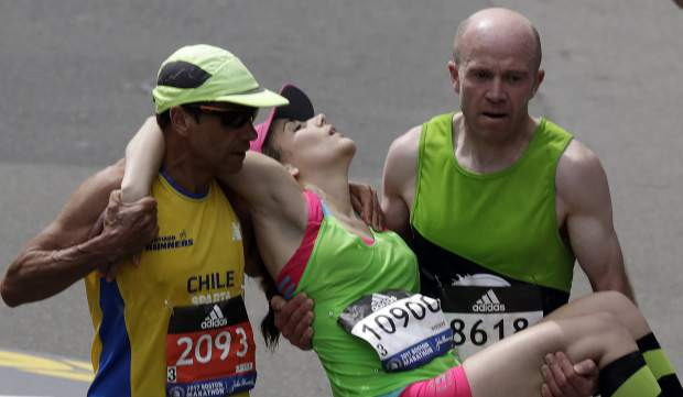 Mario Vargas, left, of Chile, and Terry Canning, right, of Britain, carry Julianne Bowe, of Hoboken, N.J., to the finish line in the the 121st Boston Marathon on Monday, April 17, 2017, in Boston. (AP Photo/Charles Krupa)