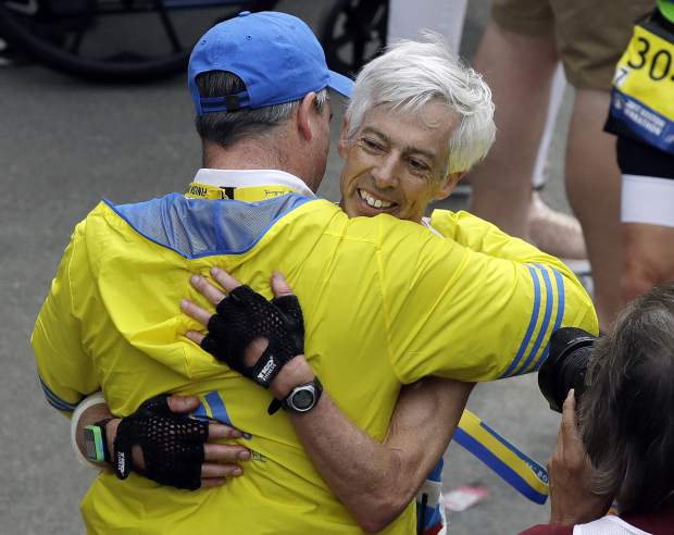 Ben Beach, of Bethesda, Md., is congratulated after completing his 50th consecutive Boston Marathon, Monday, April 17, 2017, in Boston. (AP Photo/Charles Krupa)