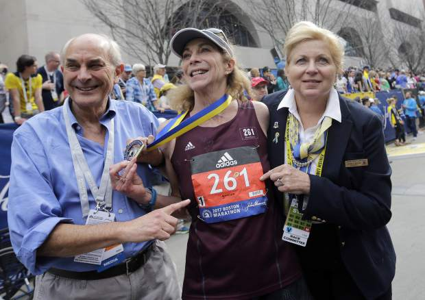 Kathrine Switzer, center, the first official woman entrant in the Boston Marathon 50 years ago, wears the same bib number after finishing the marathon on Monday, April 17, 2017, in Boston. With Switzer are her husband Roger Robinson, left, and Joann Flaminio, right, of the Boston Athletic Association. (AP Photo/Elise Amendola)