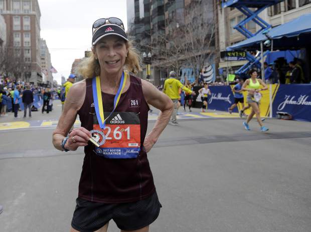 Kathrine Switzer, who was the first official woman entrant in the Boston Marathon 50 years ago, wears the same bib number and displays her medal after finishing the 121st Boston Marathon on Monday, April 17, 2017, in Boston. (AP Photo/Elise Amendola)