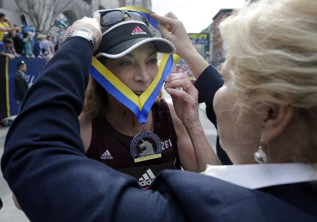 Kathrine Switzer, the first official woman entrant in the Boston Marathon 50 years ago, receives her medal from Joann Flaminio, right, of the Boston Athletic Association,after finishing the marathon Monday, April 17, 2017, in Boston. (AP Photo/Elise Amendola)