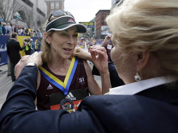 Kathrine Switzer, who was the first official woman entrant in the Boston Marathon 50 years ago, receives her medal from Joann Flaminio, right, of the Boston Athletic Association after finishing the 121st Boston Marathon on Monday, April 17, 2017, in Boston. (AP Photo/Elise Amendola)