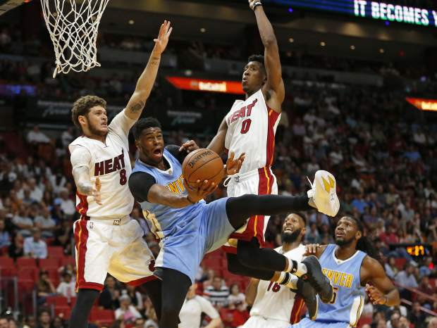 Denver Nuggets' Emmanuel Mudiay (0) is fouled when he goes up for the shot between Miami Heat's Josh Richardson (0) and Tyler Johnson (8) during the first half of an NBA basketball game, Sunday, April 2, 2017, in Miami. (AP Photo/Joel Auerbach)