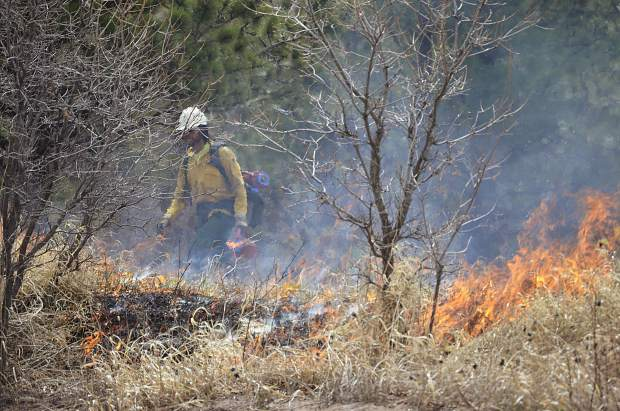 Fire crews from the Upper Colorado River Interagency Fire Management Unit light strips of flames in Avalanche Creek last April as part of a prescribed burn.