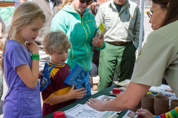 Nine-year-old Mia Alvey and Tanner (6) speak with the White River National Forest Service representatives at the Earth Day Celebration.