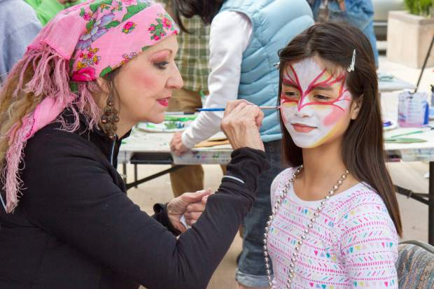 Eleven-year-old Stefani Andrade gets her face painted at the Glenwood Center for the Arts booth at the Earth Day Celebration in Centennial Park Saturday afternoon.