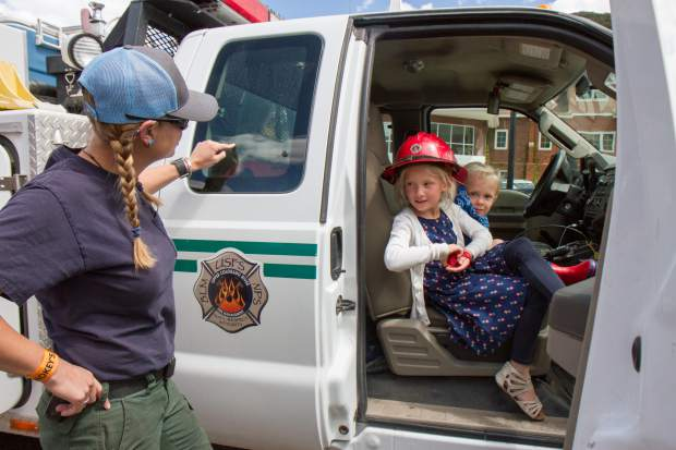 Three-year-old Hudson Campbell and his sister Harper speak with the White River National Forest representatives about forest fires and fire safety at the Earth Day Celebration in Centennial Park on Saturday afternoon.