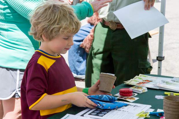Six-year-old Tanner Alvey picks up some cool stuff at the White River National Forest Service booth at the Earth Day Celebration.