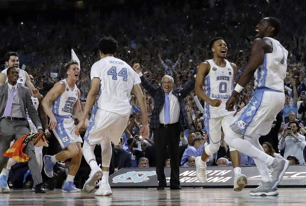 North Carolina head coach Roy Williams, middle, and players celebrate after the finals of the Final Four NCAA college basketball tournament against Gonzaga, Monday in Glendale, Ariz. North Carolina won 71-65.
