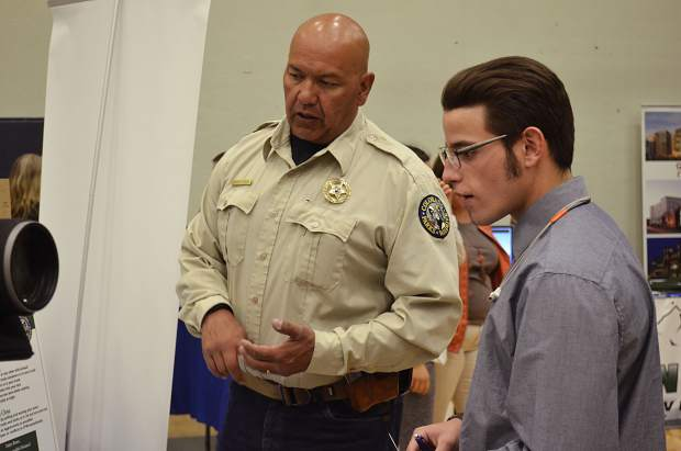 Noah Peterson, right, a senior at Yampa Mountain High School, chats with Darren Chacon of Colorado Parks and Wildlife's Glenwood Springs office.