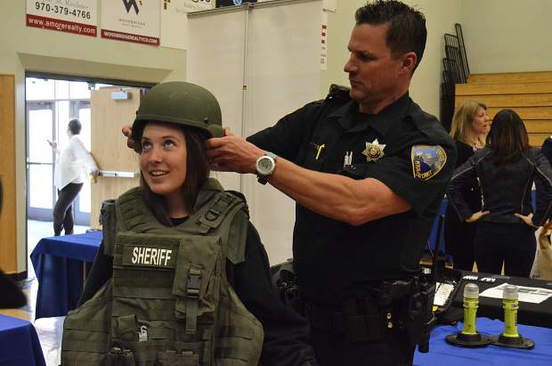 A Pitkin County sheriff's deputy fits Yampa Mountain High School freshman Jessica Lee in tactical gear at Wednesday's GlenX career expo at Roaring Fork High School.