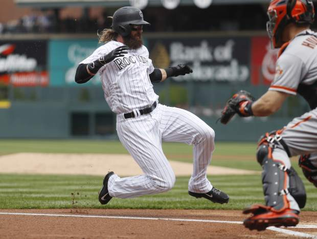 Colorado Rockies' Charlie Blackmon, left, scores on a sacrifice fly hit by Nolan Arenado as San Francisco Giants catcher Nick Hundley waits for the throw in the first inning of a baseball game Sunday, April 23, 2017, in Denver.(AP Photo/David Zalubowski)