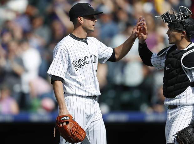 Colorado Rockies relief pitcher Chris Rusin, left, is congratulated by catcher Tony Wolters after retiring San Francisco Giants' Gorkys Hernandez for the final out in the ninth inning of a baseball game Sunday, April 23, 2017, in Denver. Colorado won 8-0. (AP Photo/David Zalubowski)