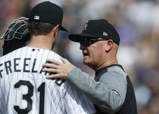 Colorado Rockies pitching coach Steve Foster, right, confers with starting pitcher Kyle Freeland after he walked San Francisco Giants' Gorkys Hernandez in the seventh inning of a baseball game, Sunday, April 23, 2017, in Denver. Colorado won 8-0. (AP Photo/David Zalubowski)