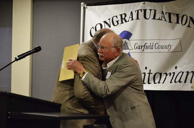 Larry Bernat embraced Commissioner Mike Samson upon winning the Building Community Award.