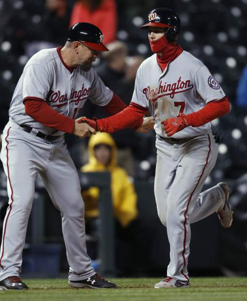 Washington Nationals third base coach Bob Henley, left, congratulates Trea Turner, who circles the bases after hitting a two-run home run off Colorado Rockies relief pitcher Jordan Lyles during the sixth inning of a baseball game Tuesday, April 25, 2017, in Denver. Washington won 15-12. (AP Photo/David Zalubowski)