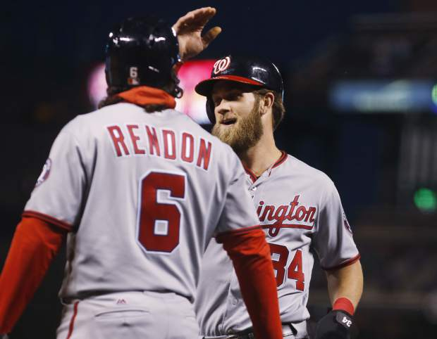 Washington Nationals' Anthony Rendon, front, congratulates Bryce Harper after he scored on a single by Daniel Murphy against the Colorado Rockies in the first inning of a baseball game, Tuesday, April 25, 2017, in Denver. (AP Photo/David Zalubowski)