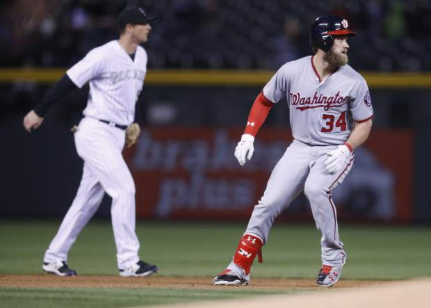 Washington Nationals' Bryce Harper, right, rounds second base after hitting a double as Colorado Rockies second baseman DJ LeMahieu looks for the throw from the outfield in the first inning of a baseball game, Tuesday, April 25, 2017, in Denver. (AP Photo/David Zalubowski)