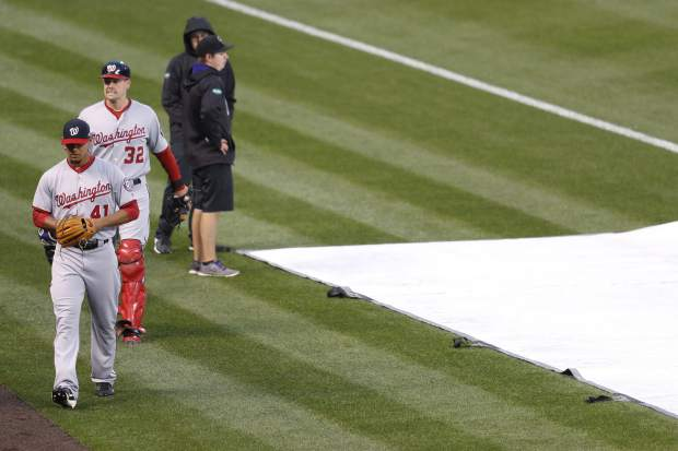 Washington Nationals starting pitcher Joe Ross, front left, and catcher Matt Wieters, back left, head from the bullpen to the dugout past field crew members, who had pulled the tarp during a weather delay before the Nationals' baseball game against the Colorado Rockies on Tuesday, April 25, 2017, in Denver. (AP Photo/David Zalubowski)