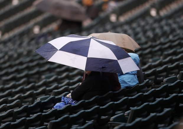 Fans sit under umbrellas as a light rain forces a weather delay before a baseball game between the Washington Nationals and tge Colorado Rockies on Tuesday, April 25, 2017, in Denver. (AP Photo/David Zalubowski)