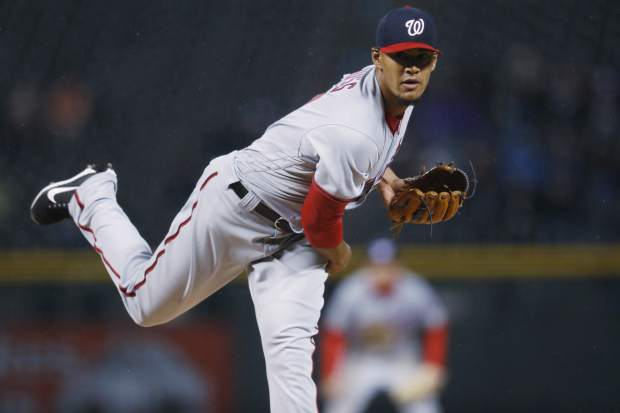 Washington Nationals starting pitcher Joe Ross delivers a pitch to Colorado Rockies' DJ LeMahieu in the first inning of a baseball game, Tuesday, April 25, 2017, in Denver. (AP Photo/David Zalubowski)