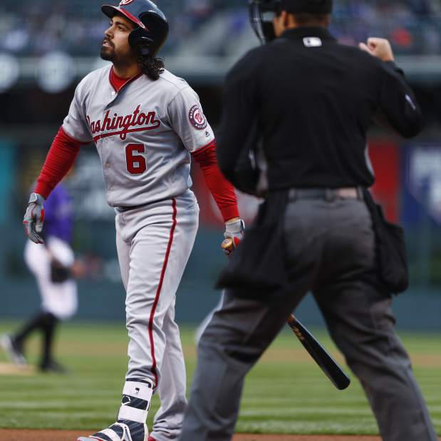 Washington Nationals' Anthony Rendon, left, reacts after striking out while swinging at pitch from Colorado Rockies starting pitcher Tyler Anderson, back, as home plate umpire Mark Wegner looks on in the first inning of a baseball game Monday, April 24, 2017, in Denver. (AP Photo/David Zalubowski)