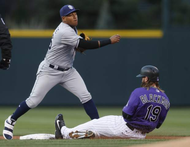 San Diego Padres second baseman Yangervis Solarte, left, forces out Colorado Rockies' Charlie Blackmon at second base on the front end of a double play after a hit by DJ LeMahieu in the first inning of a baseball game Monday, April 10, 2017, in Denver. (AP Photo/David Zalubowski)