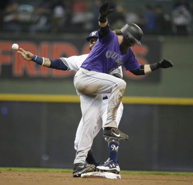 Colorado Rockies' Charlie Blackmon is safe at second but Milwaukee Brewers' Jonathan Villar throws out Rockies' DJ LeMahiew af first base during the third inning of an opening day baseball game Monday, April 3, 2017, in Milwaukee. (AP Photo/Jeffrey Phelps)