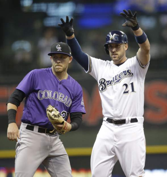 Milwaukee Brewers' Travis Shaw (21) reacts after his run scoring double against the Colorado Rockies during the fifth inning of an opening day baseball game Monday, April 3, 2017, in Milwaukee. At left is Rockies' Travor Story. (AP Photo/Jeffrey Phelps)