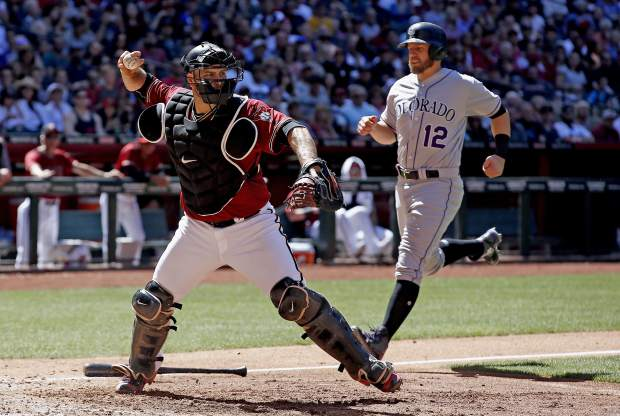 Arizona Diamondbacks' Chris Iannetta, left, throws to first base after forcing out Colorado Rockies' Mark Reynolds (12) at home plate during the fifth inning of a baseball game Sunday, April 30, 2017, in Phoenix. Rockies' German Marquez was safe at first base on the play. (AP Photo/Ross D. Franklin)