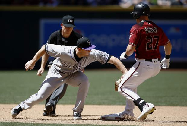 Arizona Diamondbacks' Brandon Drury (27) arrives safely at second base with a double as Colorado Rockies' DJ LeMahieu, left, applies a late tag while umpire Toby Basner, back left, watches during the fourth inning of a baseball game, Sunday, April 30, 2017, in Phoenix. (AP Photo/Ross D. Franklin)