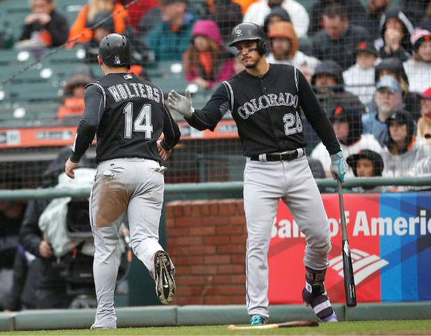 Colorado Rockies' Nolan Arenado (28) congratulates teammate Tony Wolters (14) after he scored a run on a single by DJ LeMahieu against the San Francisco Giants during the second inning of a baseball game, Sunday, April 16, 2017, in San Francisco. (AP Photo/Tony Avelar)