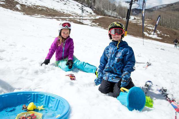 Kaylie Howell and Jake Hardy play at the Mini Pond Skim set up for kids at the base of the Mountain. Due to the lack of snow at the base of the mountain, Sunlight was unable to create a life-sized pond skim for the closing day on Sunday.