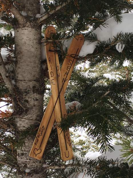 Crossed wooden skis are part of a memorial that hang from a tree at the intersection of the Lower Boneyard run and Frosty's Freeway at Breckenridge Ski Resort in tribute to skier Sean Haberthier, who died at the location on Jan. 12, 2017.