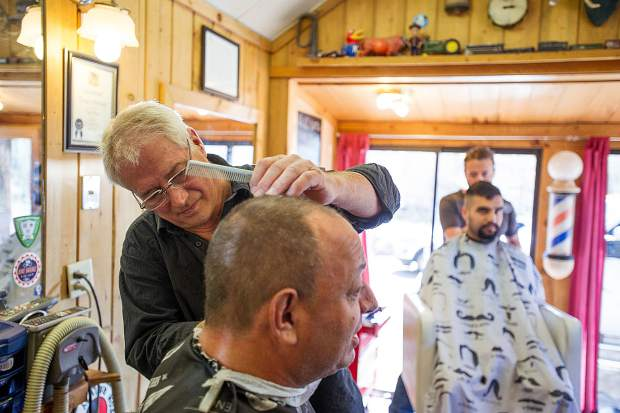Lonnie Bones, cutting hair in the front, and his son Chad, rear, are the third and fourth generation of barbers in the family. A Bones has been cutting hair since 1914.