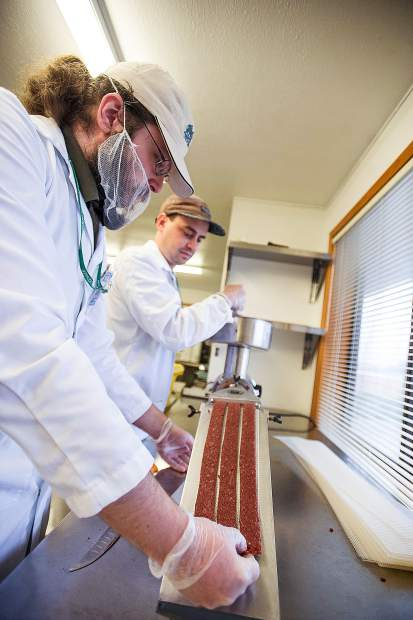 Cannabis Queen Jerky employees Justin Carleton, left, and Zach Darling tending a machine that forms the buffalo meat into strips before it is dried and packaged for sale.