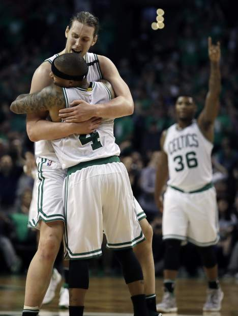 Boston Celtics guards Isaiah Thomas (4) and Marcus Smart (36) celebrate with center Kelly Olynyk (41) after Olynyk sank a basket during the fourth quarter of Game 7 of a second-round NBA basketball playoff series against the Washington Wizards, Monday, May 15, 2017, in Boston. (AP Photo/Charles Krupa)